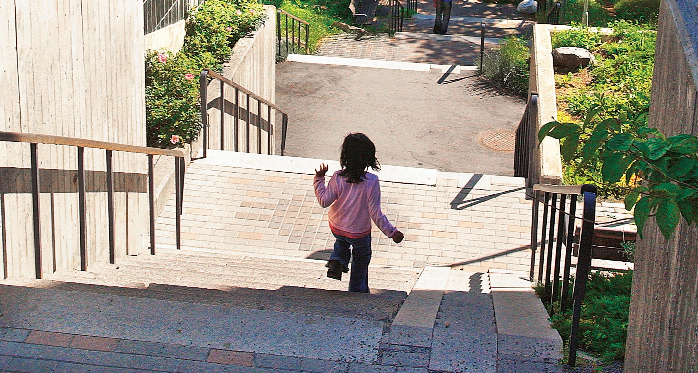Flicka som springer nedför en trappa utomhus